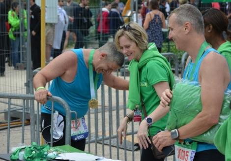 медаль участника Парижского марафона и радость от того, что он это сделал